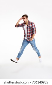 Full length portrait of a young funny man walking while jumping isolated over white background
