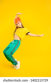 A full length portrait of a young girl dancing in the studio over the yellow background. Sport fashion for teenagers.