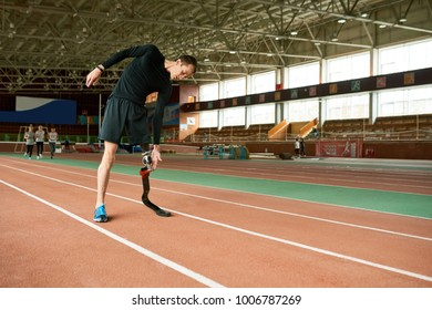Full length portrait of young handicapped athlete with artificial foot warming up before running practice in modern gym stretching to sides, copy space