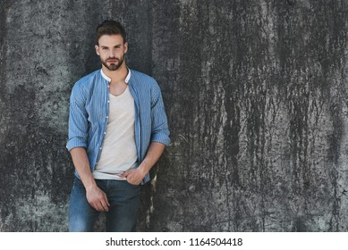 Full length portrait of young handsome model dressed in casual outfit and standing on street and looking away on copy space area for your advertising text message or promotion