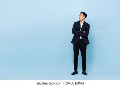 Full length portrait of young handsome southeast Asian businessman with arms crossed looking up sideway to copy space on light blue studio background
