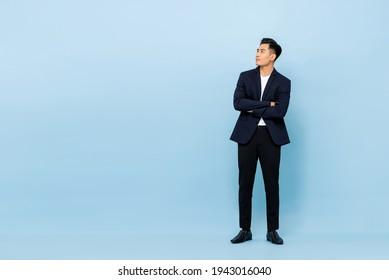 Ganzes Portrait von jungen gut aussehenden südostasiatischen Geschäftsleuten, deren Arme nach oben gekreuzt sind, um Platz auf hellblauem Studiohintergrund zu kopieren