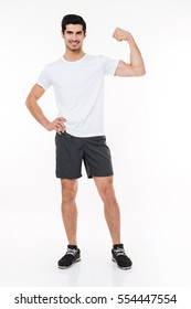 Full length portrait of a young handsome smiling sportsman showing biceps isolated on a white background