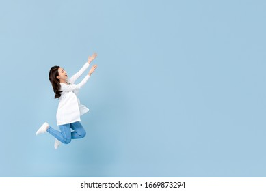Full length portrait of young happy Asian woman floating in mid-air with hands opening to blank space beside in blue isolated studio background