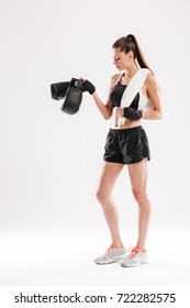Full length portrait of a young healthy sportswoman with a towel on her neck standing and holding boxing gloves isolated over white background