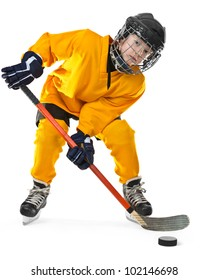 Full length portrait of young hockey player in yellow uniform, with stick and puck. On the white background