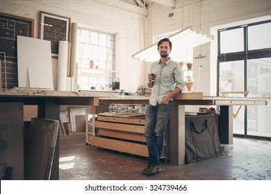 Full length portrait of a young male designer standing comfortably in his naturally lit workshop holding his morning cup of coffee and smiling at the camera