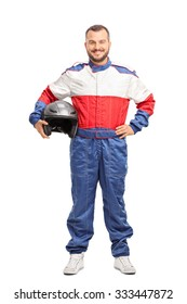 Full length portrait of a young male car racer in overalls holding a helmet and looking at the camera isolated on white background