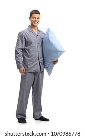 Full length portrait of a young man in pajamas holding a pillow isolated on white background