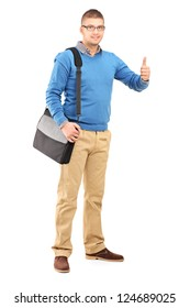 Full length portrait of a young man with a shoulder bag giving a thumb up isolated on white background