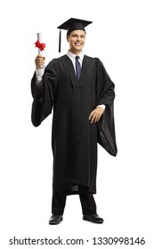 Full length portrait of a young man in a black graduation gown and cap holding a diploma isolated on white background