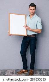Full length portrait of a young man holding blank board over gray background