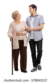 Full length portrait of a young man helping a mature woman with a walking cane isolated on white background