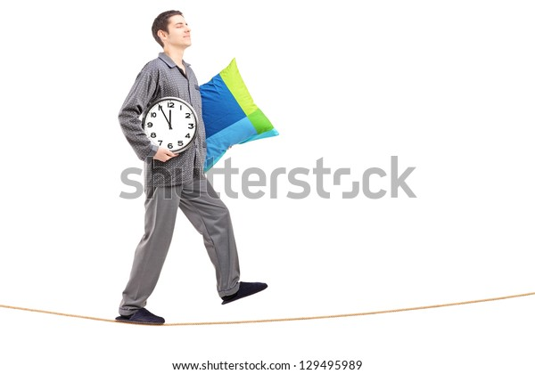 Full length portrait of a young man with pillow and clock sleepwalking on a rope isolated against white backgroun