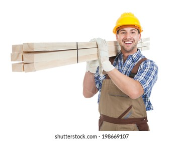 Full length portrait of young manual worker carrying wooden planks over white background