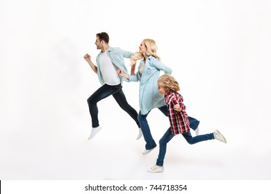 Full length portrait of a young modern family with a child running together isolated over white background