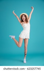Full length portrait of a young playful woman wearing hat and dress posing with hands raised on one hand isolated over blue background