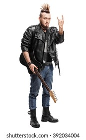 Full length portrait of a young punk rocker holding a guitar and making a hardcore hand gesture isolated on white background