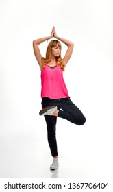 Full length portrait of a young red-haired fitness model in pink sportswear doing yoga or pilates exercise, Vrikshasana, tree pose, hands in Namaste, front view, studio shot, isolated