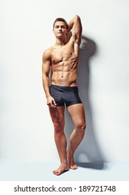Full length portrait of a young sexy muscular male model in underwear against white wall in sensual pose his hand behind his head