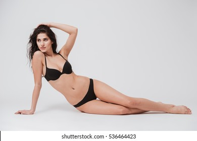 Full length portrait of a young sexy woman in lingerie laying on the floor isolated on white background