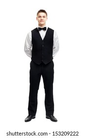 Full length portrait of young smiling waiter standing with hands behind his back isolated on white background