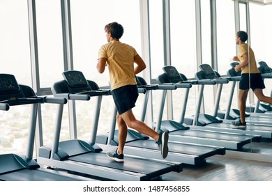 Full length portrait of young sports man running on a treadmill at gym. Fitness, workout and and healthy lifestyle concept. Full length