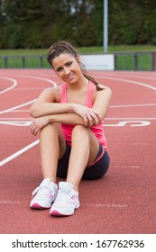 Full length portrait of a young sporty woman sitting on the running track
