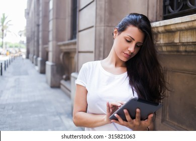 Full length portrait of a young stylish hipster girl working on her digital tablet computer while standing on the street in urban setting,gorgeous female tourist using touch pad for navigation in city