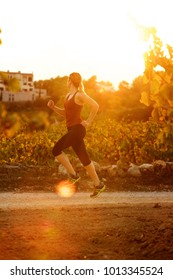 Full length portrait of young woman running on path during sunset