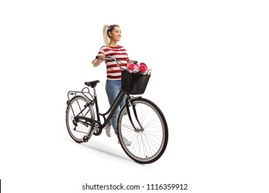 Full length portrait of a young woman pushing a bicycle isolated on white background