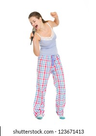 Full length portrait of young woman in pajamas singing in microphone