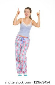 Full length portrait of young woman in pajamas pointing up on copy space