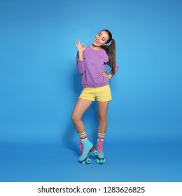 Full length portrait of young woman with roller skates on color background