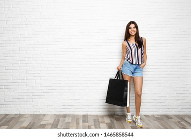 Full length portrait of young woman with paper bags near white brick wall, space for text