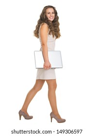 Full length portrait of young woman with laptop going sideways