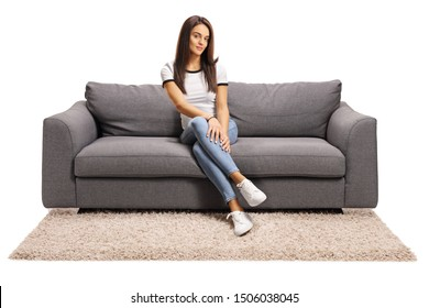 Full length portrait of a young woman sitting on a gray sofa isolated on white background
