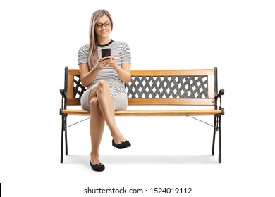 Full length portrait of a young woman sitting on a bench and using a mobile phone isolated on white background