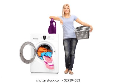 Full length portrait of a young woman holding an empty basket and leaning on a laundry detergent on top of a washing machine isolated on white background