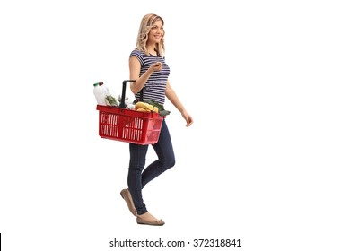 Full length portrait of a young woman walking and carrying a shopping basket full of groceries isolated on white background