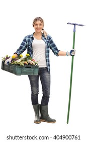 Full length portrait of a young woman holding a rack of flowers and a gardening rake isolated on white background