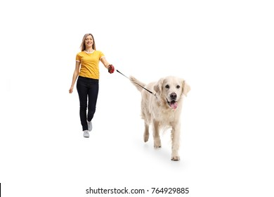 Full length portrait of a young woman walking a dog isolated on white background