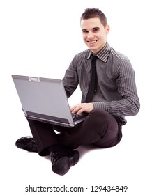 Full length pose of young businessman sitting on the floor and writing on his laptop, isolated on white background