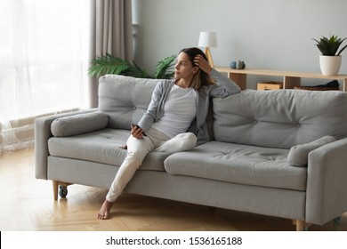 Full length positive dreamy young biracial girl leaning on comfortable couch, holding mobile phone in hands, looking at window, thinking of future date, meeting with friends or enjoying calm moment.