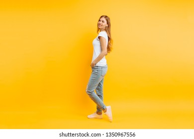 Full length, positive girl in a white T-shirt walking poses posing on a yellow background