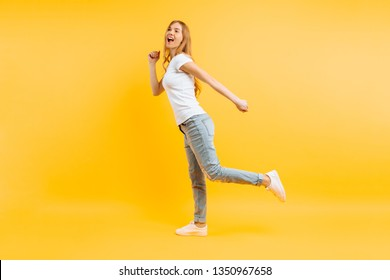 Full length, positive girl in white t-shirt walking on a yellow background.
