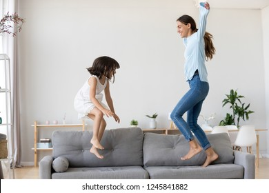 Full length positive mother and little daughter having fun jumping together on sofa in living room at home. Adorable girl playing enjoying active weekends with elder sister nanny or loving mom indoors