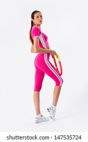 Full length potrait of young female athlete exercising with hula-hoop at white background