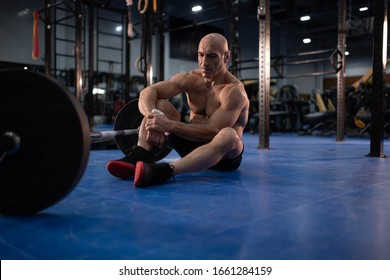 Full length powerful elderly sportsman with sweaty muscular body sitting near barbell and resting during functional training in gym