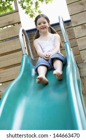 Full length of pretty young girl playing on slide in park